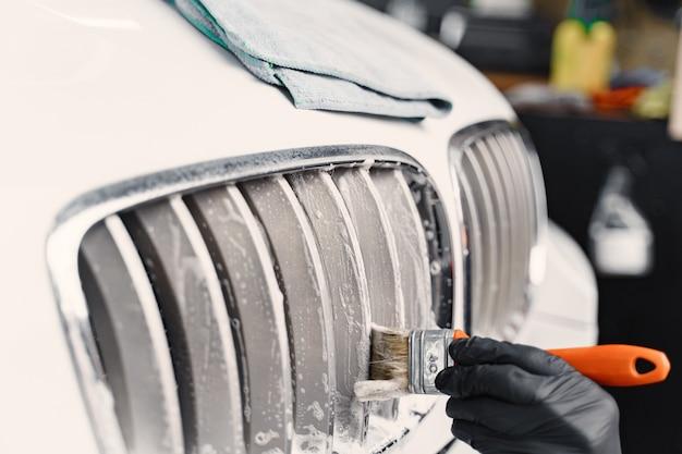 Mano masculina con esponja de espuma lavando coche