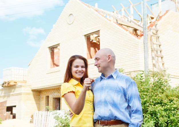 Mano masculina y femenina, llaves de la casa feliz edificio verde al aire libre