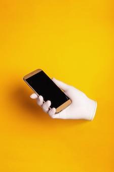 Mano masculina en un guante médico sostiene un teléfono sobre un fondo amarillo