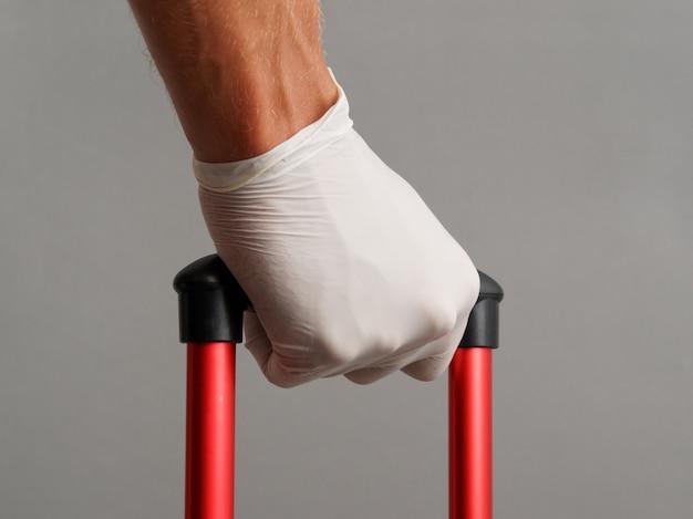 La mano masculina en guante sostiene la maleta de la manija. concepto de viaje durante el coronavirus.