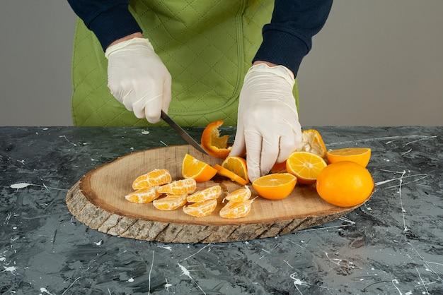 Mano masculina en guantes cortando jugosa naranja sobre mesa de mármol.