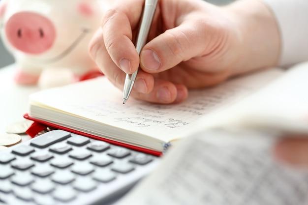 Mano masculina haciendo algunas notas con bolígrafo plateado sobre papel sobre flujo de caja