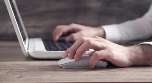 Mano masculina haciendo clic en el ratón de la computadora. internet. negocio. tecnología