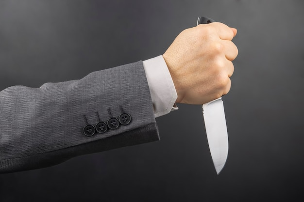 Mano masculina de un hombre de negocios sostiene un cuchillo