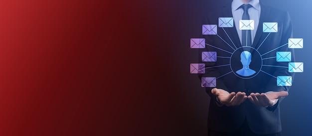 Mano masculina con icono de letra, iconos de correo electrónico. póngase en contacto con nosotros por correo electrónico del boletín y proteja su información personal del correo no deseado. centro de atención al cliente contáctenos. email marketing y newsletter.
