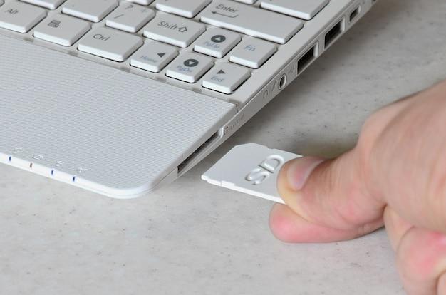 Una mano masculina inserta una tarjeta sd compacta blanca en el correspondiente