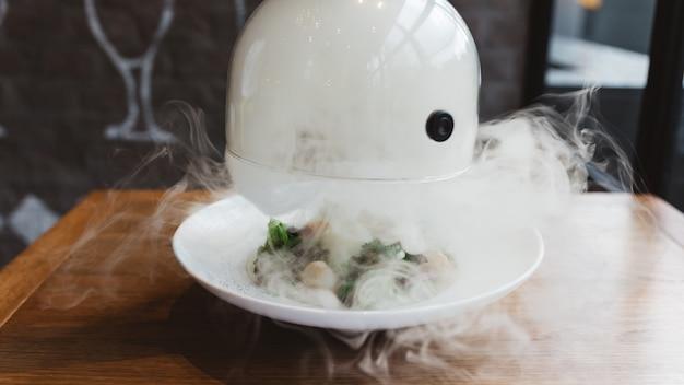 La mano masculina se levanta para levantar la campana de vidrio de un plato con comida caliente y humo en movimiento en el restaurante.