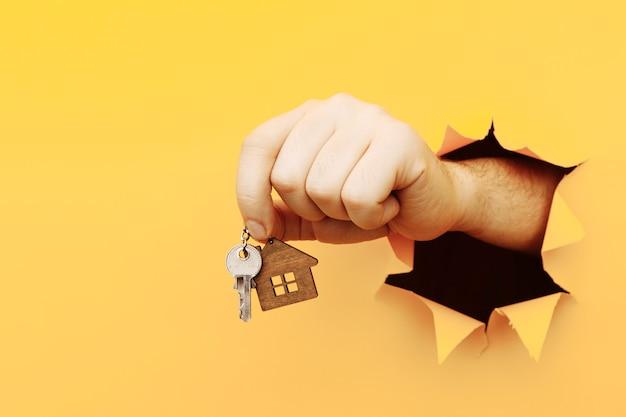Mano masculina con llaves de casa a través de un agujero en la pared de papel amarillo concepto de venta y alquiler de casa