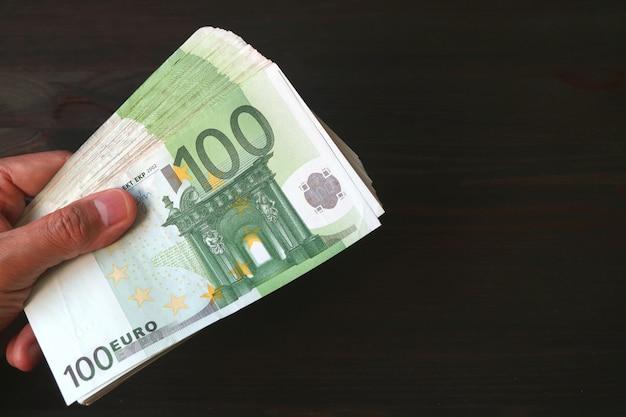 Mano masculina con manojo de 100 billetes en euros en negro