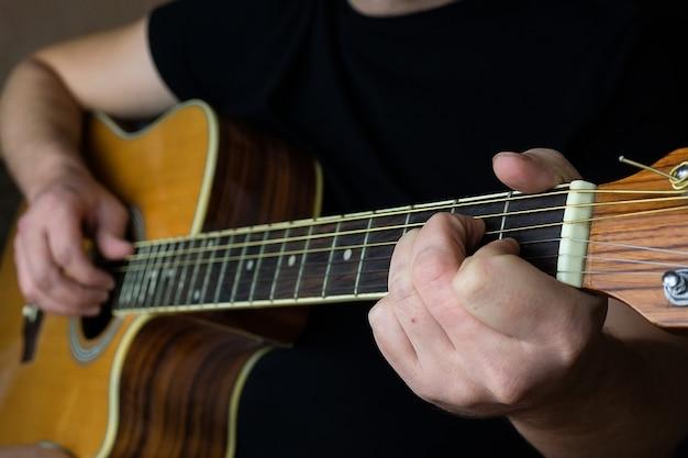 Una mano masculina mientras toca una guitarra electroacústica.