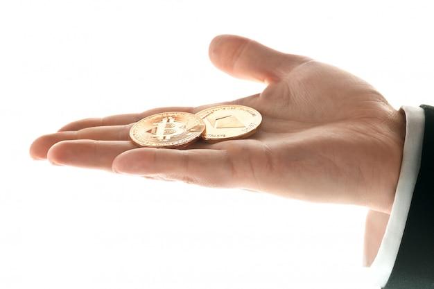 Mano masculina con monedas de oro bitcoin