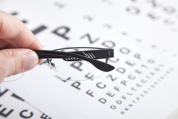 Mano masculina mostrando anteojos. tabla de prueba ocular