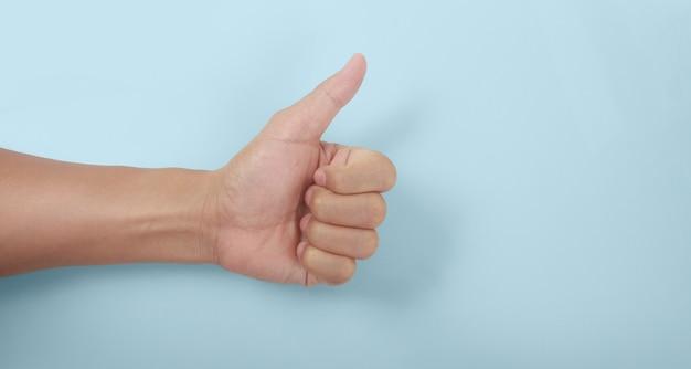 Mano masculina mostrando los pulgares para arriba signo contra