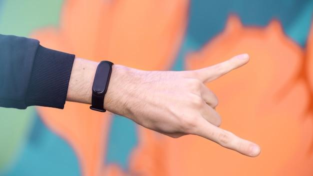 Una mano masculina mostrando signo de rock con pulsera de fitness, fondo multicolor