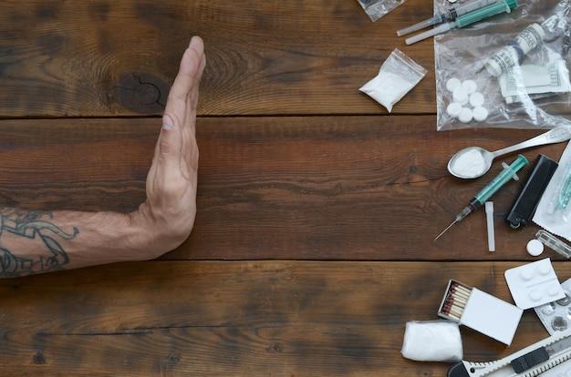 La mano masculina muestra el signo de parada a todas las definiciones de narcóticos. muchas píldoras de drogas y polvo en la mesa de madera
