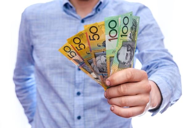 Mano masculina ofreciendo billetes de dólar australiano aislado en blanco