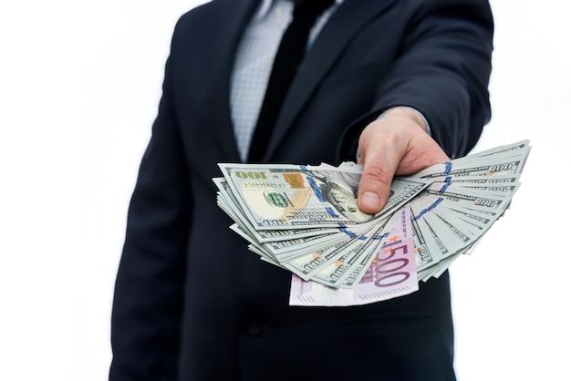 Mano masculina ofreciendo montón de billetes de dólar y euro
