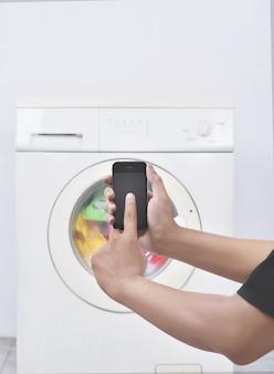 Mano masculina opera lavadora con su teléfono móvil.
