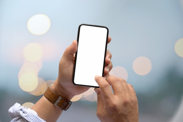 Mano masculina y pantalla móvil en blanco.