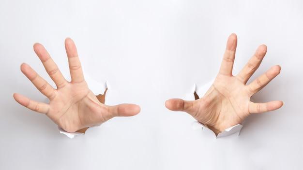 Mano masculina perforando a través del papel