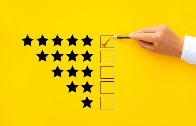 Mano masculina poniendo marca de verificación una casilla de verificación en la calificación de cinco estrellas. aumentar el concepto de empresa de calificación.