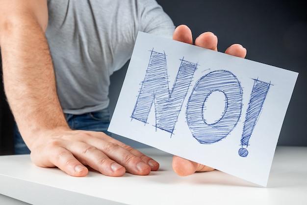 La mano masculina del primer sostiene una tarjeta blanca con la palabra no. fracaso desacuerdo protesta.