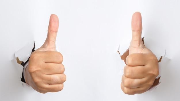 Mano masculina con pulgar arriba gesto que perfora a través del papel