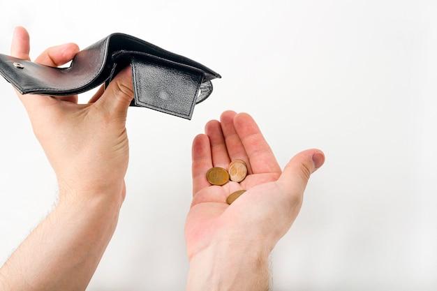 Mano masculina que abre una cartera y cuenta monedas en el fondo blanco. crisis económica mundial. problema financiero sin trabajo, concepto de quiebra.