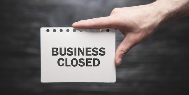 Mano masculina que muestra el texto de negocios cerrados en papel.