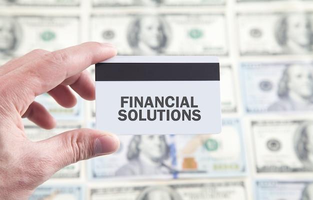 Mano masculina que muestra el texto de soluciones financieras en la tarjeta de crédito.