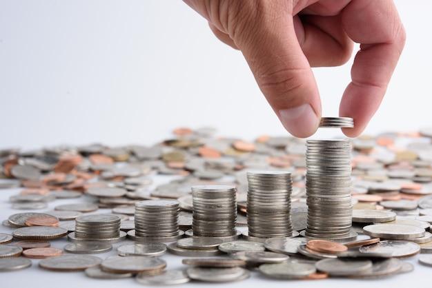 Mano masculina que pone monedas con dinero pila crecimiento creciente crecimiento ahorrar dinero, negocio de finanzas del concepto