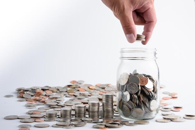 Mano masculina que pone monedas en tarro con el dinero creciente del ahorro del crecimiento del paso de la pila del dinero, bu