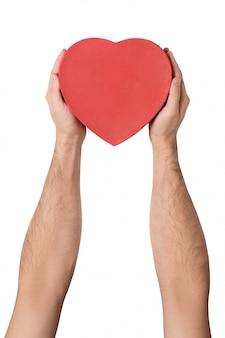 Mano masculina que sostiene una caja roja en forma de corazón.