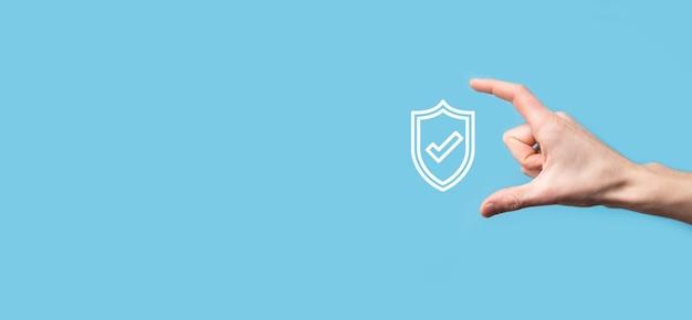 Mano masculina que sostiene el escudo de protección con un icono de marca de verificación en la superficie azul