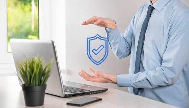 Mano masculina que sostiene el escudo protector con un icono de marca de verificación. seguridad de la red de protección