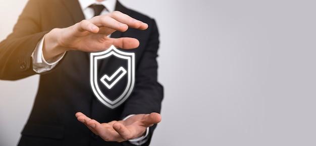 Mano masculina que sostiene el escudo protector con un icono de marca de verificación sobre fondo azul. equipo de seguridad de red de protección y seguro su concepto de datos.