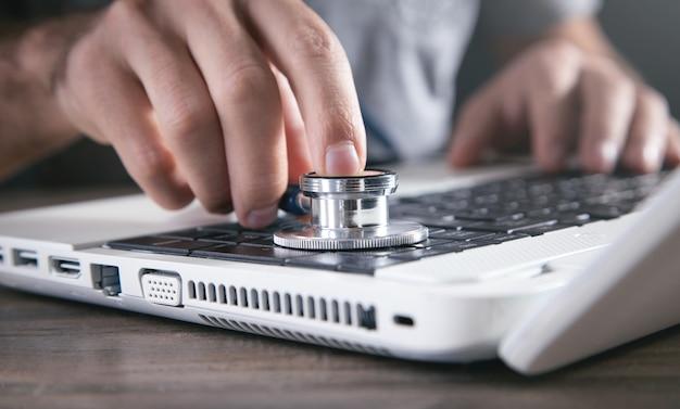 Mano masculina que sostiene el estetoscopio en un teclado de computadora portátil.
