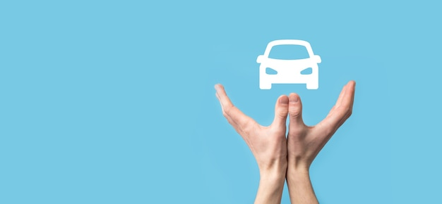 Mano masculina que sostiene el icono automático del coche en la superficie azul