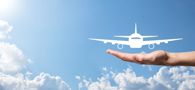Mano masculina que sostiene el icono de avión avión sobre fondo azul. compra de boletos de banner.nline.iconos de viaje sobre planificación de viajes, transporte, hotel, vuelo y pasaporte.concepto de reserva de boletos de vuelo.