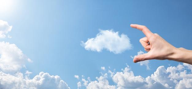 Mano masculina que sostiene el icono de la casa sobre fondo azul. seguro de propiedad y concepto de seguridad concepto de bienes raíces condiciones climáticas, nubosidad bandera con espacio de copia.