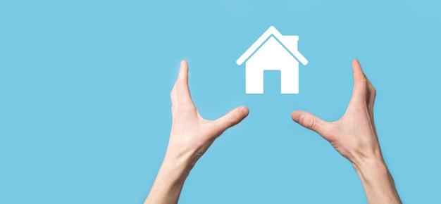 Mano masculina que sostiene el icono de la casa sobre fondo azul. seguro de propiedad y concepto de seguridad concepto de bienes raíces.