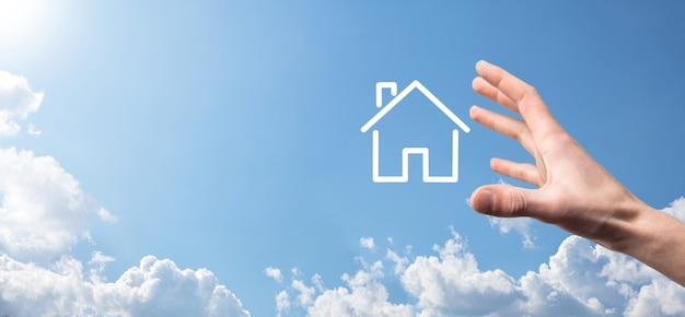 Mano masculina que sostiene el icono de la casa sobre fondo azul. seguro de propiedad y concepto de seguridad inmobiliaria.