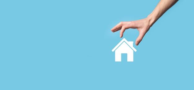 Mano masculina que sostiene el icono de la casa en superficie azul