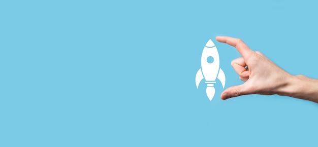 Mano masculina que sostiene el icono del cohete que despega, lanzamiento sobre fondo azul. el cohete se está lanzando y volando, la puesta en marcha de un negocio, el marketing de iconos en la interfaz virtual moderna.