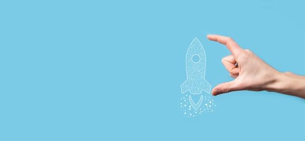 Mano masculina que sostiene el icono de cohete transparente digital. concepto de negocio de inicio. el cohete se está lanzando y se eleva volando. concepto de idea de negocio.