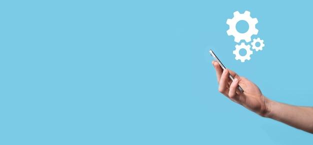 Mano masculina que sostiene el icono de engranajes dentadas, icono de mecanismo en pantallas virtuales sobre fondo azul. concepto de negocio de sistema de proceso de tecnología de software de automatización. bandera.