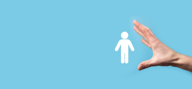 Mano masculina que sostiene el icono humano sobre fondo azul. recursos humanos gestión de recursos humanos reclutamiento empleo headhunting concept.seleccione el concepto de líder de equipo. mano masculina, haga clic en el icono de hombre. bandera, copia spase.