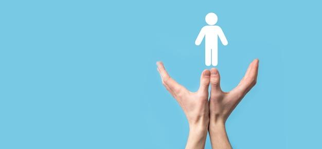 Mano masculina que sostiene el icono humano en la superficie azul. recursos humanos