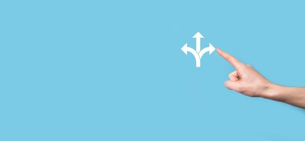 Mano masculina que sostiene el icono con el icono de tres direcciones sobre fondo azul.n dudo de tener que elegir entre tres opciones diferentes indicadas por flechas que apuntan en dirección opuesta concepto de tres formas