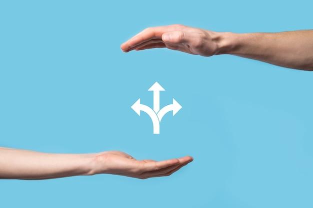 Mano masculina que sostiene el icono con el icono de tres direcciones sobre fondo azul.no dude en tener que elegir entre tres opciones diferentes indicadas por flechas que apuntan en el concepto de dirección opuesta de tres maneras.